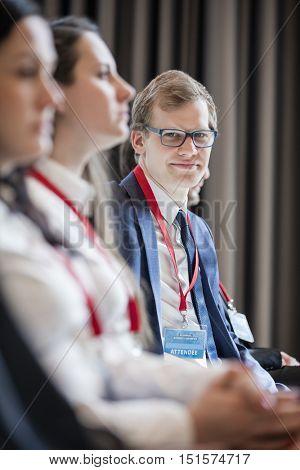 Portrait of confident businessman sitting in seminar hall