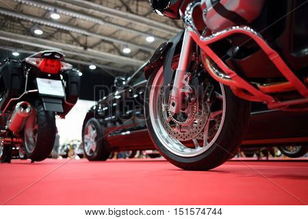 Black bikes for cortege, car are on red carpet in exhibition, close up