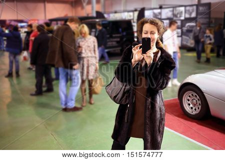 Happy pretty woman in fur coat shoots by phone at exhibition