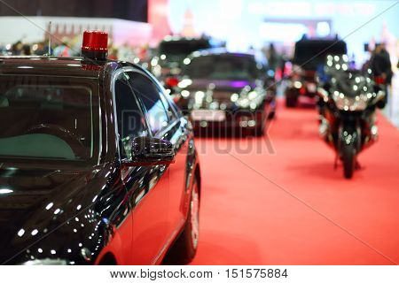 Black car of cortege with blinker on red carpet and bike exhibition