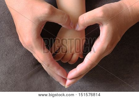 A mother holds the hand of a small child's hands creating a heart