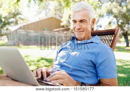 Senior man with notebook sitting in the park