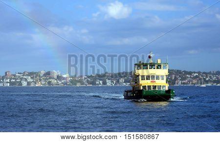 Sydney Australia - March 23 2013. Transport Sydney Ferry boat heading to Sydney Cirqular Quay with passengers onboard during rainbow.