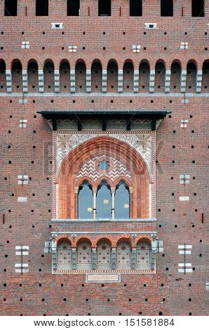 MILAN, ITALY - JUNE 9, 2015: Detail of the Sforza castle in Milan Italy. Arched window decorated with ornaments and arched insets on a red brick wall.