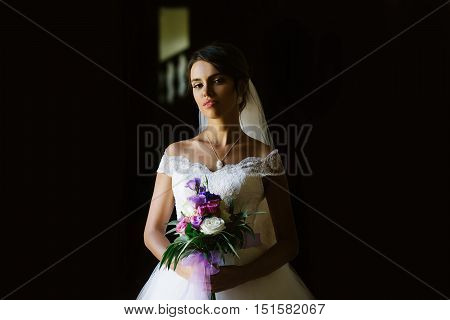 young sexy woman or girl bride with makeup on pretty face and veil in hair holding wedding bouquet or posy of eudtoma and rose flowers in white dress on dark background
