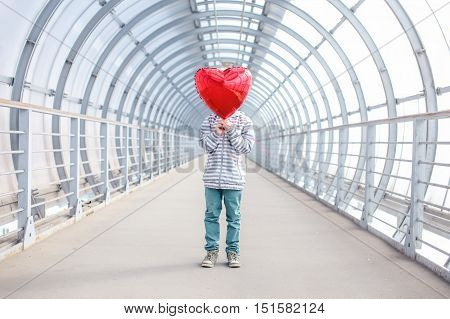 kid with a red balloon as an heart. boy hid his face behind a red balloon. the concept of teen's love, hiding feelings.Valentine's day, heart-shaped balloon