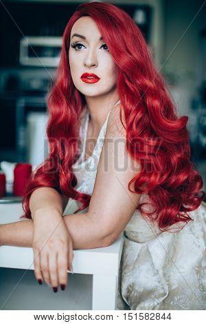 Young girl with long red hair inside looking nice