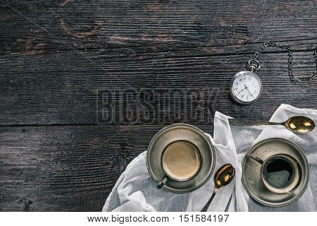 Metal vintage cups of coffee and pocket watch on the wooden table. Flat lay