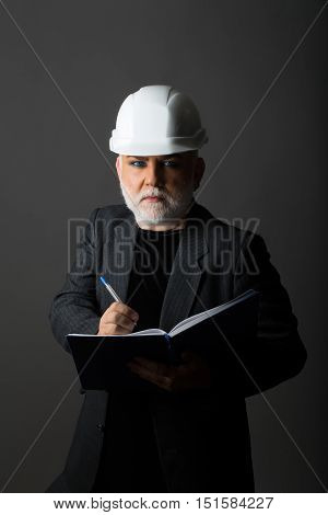 Handsome bearded old man with silver moustache on serious face in white hard hat and suit with notebook and pen on gray background