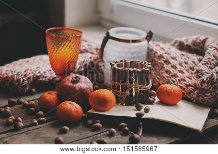 cozy winter morning at home with fruits nuts and candles selective focus vintage toned