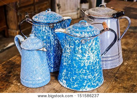Antique graniteware, speckleware, enamelware, agateware, coffee pots. Four pots in all. Two cobalt blue and white swirl, one grey and white mottled one light blue and white speckled.