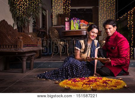 Indian young couple in traditional wear lighting oil lamp and celebrating Diwali or deepavali, fesitval of lights at home. Husband holding a plate full of oil lamp indoors near flower rangoli