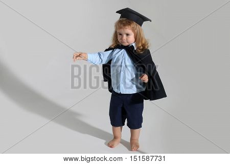 Small boy child with long blond hair in blue shirt black graduation gown and cap isolated on white background
