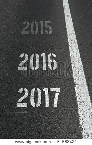 2017 Happy New Year Continuous Year Numbers Count on asphalt road selective focus