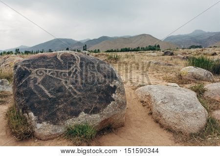 Petroglyphs on stones. In are far mountains are visible