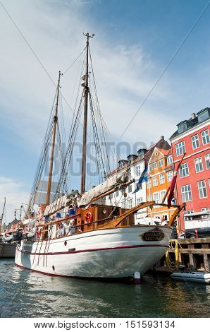 Copenhagen Denmark - August 5 2010: Old sailing boat in Nyhavn. Nyhavn is a historic waterfront. It is lined by colorful 17th and 18th century townhouses and bars cafes and restaurants. In its function as a 'heritage harbor' the canal has many historical
