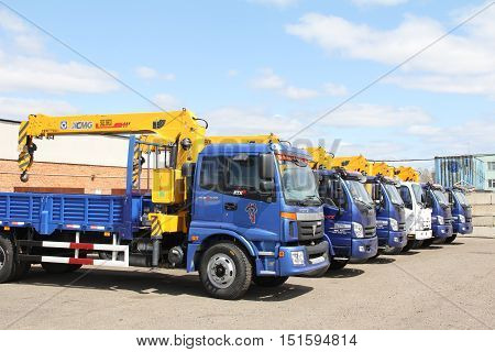 A blue foton flatbed truck with yellow crane arm is in the parking lot - Russia Moscow 30 August 2016