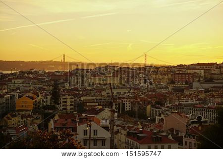 Aerial view of the capital city of Portugal - Lisbon (Lisboa) during the orange summer sunset over the river and famous bridge (25 de Abril Bridge) similar to Bay Bridge in San Francisco