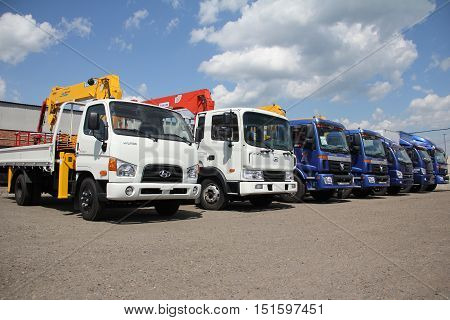 White, Blue Flatbed Trucks With Crane Arm Is In The Parking Lot - Russia, Moscow, 30 August 2016