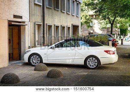 STRASBOURG FRANCE - JUL 4 2016: Luxury Mercedes-Benz CLK convertible car entering through garage door in modern calm city