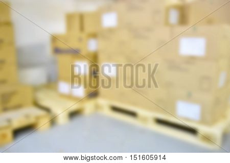 Blurred background warehouse. Abstract blurry warehouse storing. The interior of the warehouse with boxes and pallets.