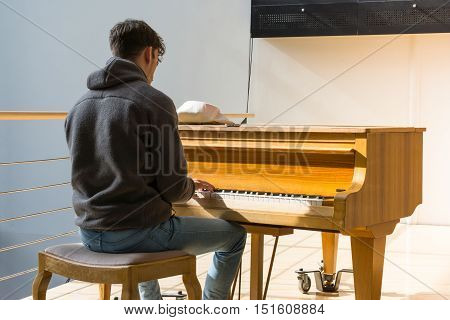 Young Man Hoody Jeans Sitting Playing Instrument Piano Keys Music Public Inside