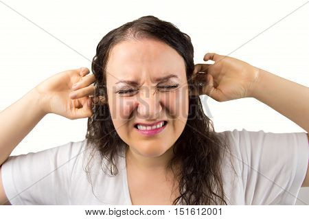 woman with hands in the ears disturbed with loud noise