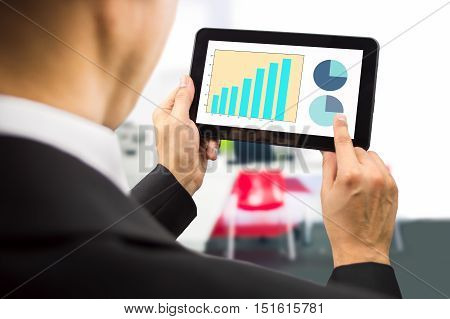 bussinesman looking at the stock market data on a tablet on the office.All screen content is designed by us and not copyrighted by others and created with wacom tablet and ps