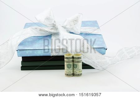 Gift wrapped book and lab notebooks placed with dollar currency reflects investment in education and learning. Savings through 529 and College Savings Plans through gifting. Horizontal image with white background and copy space.