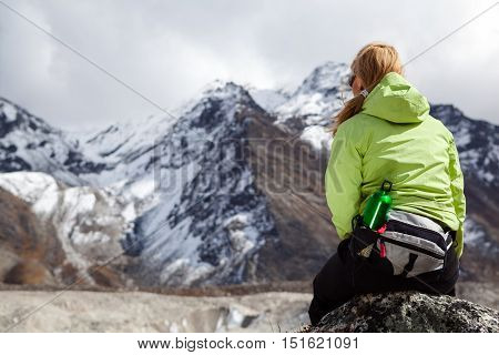 Woman hiker relaxing on rocks in Himalaya Mountains Nepal. Young Girl Looking at Beautiful Inspirational Landscape. Recreation Meditating Outdoors in High Mountains in Nepal.