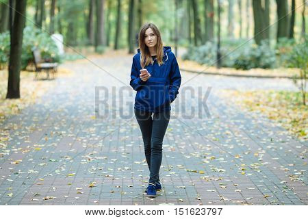 Stylish Sporty Brunette Woman In Trendy Urban Outwear Posing At Forest City Park On Cold Rainy Fall