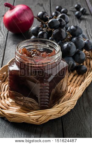 Red onion jam (onion confiture) with grapes in glass jars and ingredients for its preparation in a wicker basket on a wooden table. French cuisine. Selective focus vertical