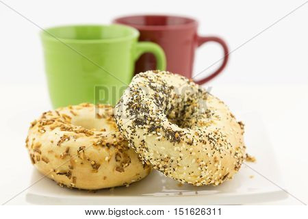 Two bagels on white plate with red and green mugs behind. Selective focus on breakfast bread.