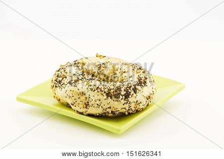 One everything bagel placed on green plate. Copy space at top. Horizontal image.