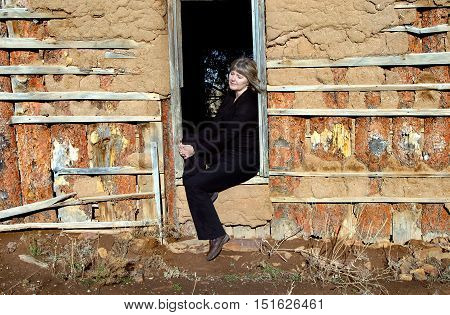 Mature female rests in doorway of old adobe home. Her eyes are closed and she trying to imagine and absorb the story and history of the abandoned home.