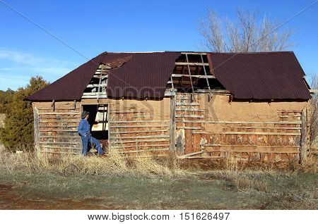 Man stands in doorway of an abandoned adobe home. He is wearing jeans and cowboy hat.
