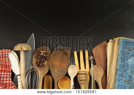 Kitchen utensils on wooden table. Tools for cook on black wooden background.