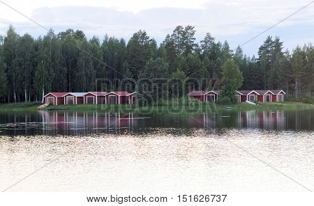 Group of red boathouse reflecting in the water birch trees in the background