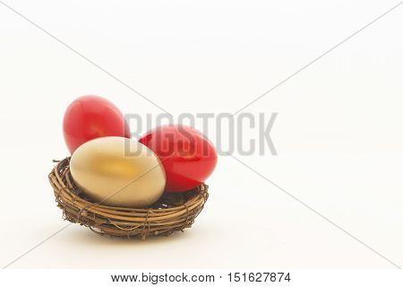 Two red eggs and one gold egg in nest reflect important choices in business and investing. Copy space on white background.