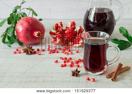 Cap of pomegranate juice or cocktail, ripe pomegranate, slices, seeds, cinnamon, star anise, glass jug on a light white wooden background. Pomegranate juice or cocktail and pomegranates. Horizontal.