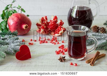 Cap of pomegranate juice or cocktail, ripe pomegranate, slices, seeds, cinnamon, star anise, jug, fir branches, heart on light white wooden background. Pomegranate juice cocktail, pomegranates, heart
