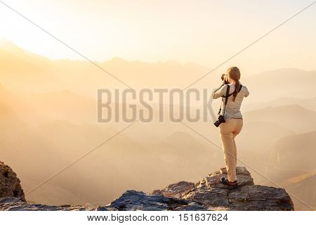 A woman is taking photos of Al Hajar Mountains in Oman at sunset