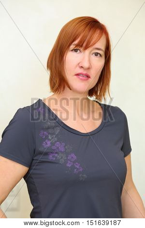 Portrait of serious middle aged woman with red hair in grey t-shirt
