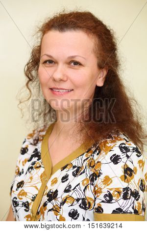 Portrait of smiling happy curly woman looking at camera in home robe