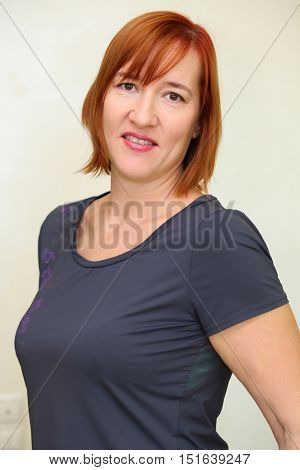 Portrait of smiling middle aged woman with red hair in grey t-shirt