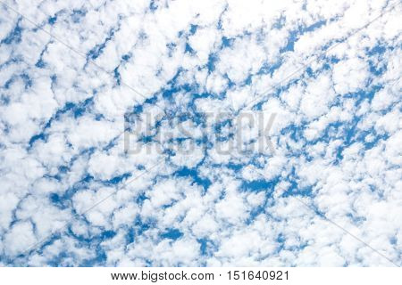 Cirrocumulus clouds as small rounded puffs appear in long rows high in the sky. Nature abstruct background.