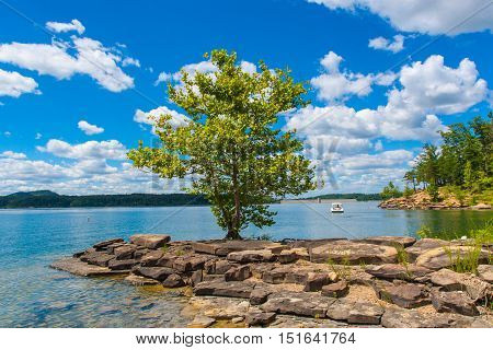 Summer view of local lake Cave Run with beautiful forest on lake hillside shore and dramatic cloudscape sky in Kentucky USA