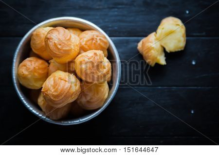 close up Cream Puffs on wooden background.