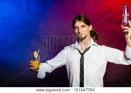 Liquor drinking party flair bartending concept. Tapster enjoying alcohol beverage. Young male barman prepares cocktail with orange juice.