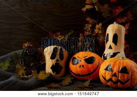 Halloween decorated pumpkins on dark rustic background copy space. Halloween symbol jack-o-lantern background. Halloween decoration.